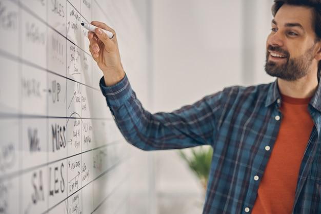 Gai jeune homme en chemise à carreaux travaillant sur la stratégie du projet et souriant