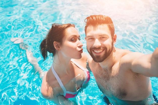 Gai jeune homme et dame au repos pendant la piscine en plein air. couple dans l'eau. les gars font un selfie d'été