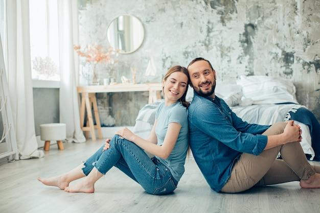Gai jeune homme et femme assis pieds nus dans des vêtements décontractés à la maison et souriant photo stock