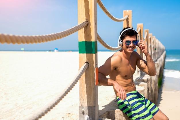 Gai jeune homme se détendre après l'entraînement du matin sur la belle plage
