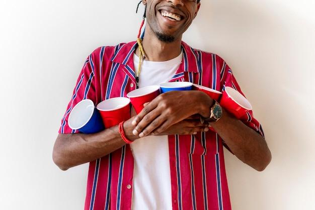 Gai jeune homme tenant des tasses rouges et bleues