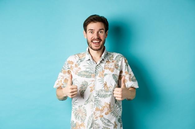 Gai mec montrant les pouces vers le haut en vacances, louant l'agence de voyages, debout en chemise d'été sur fond bleu.