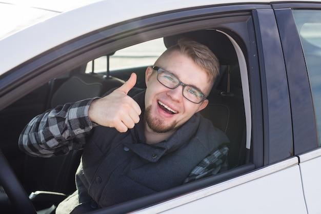 Gai mec occasionnel souriant joyeusement montrant les pouces vers le haut assis dans une grande voiture blanche