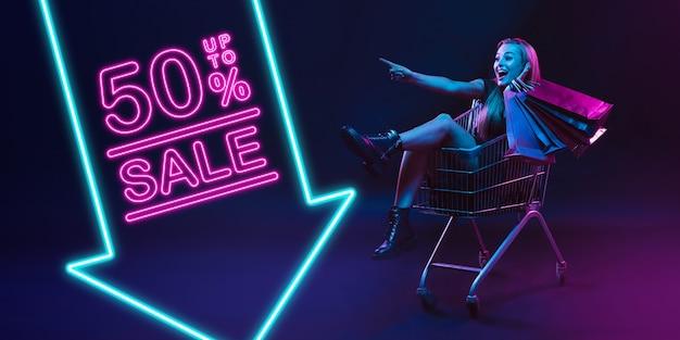Gai, pointant. portrait de jeune femme en néon sur fond de studio sombre. émotions humaines, vendredi noir, cyber lundi, achats, ventes, concept financier. espace de copie. publication transparente pour instagram.
