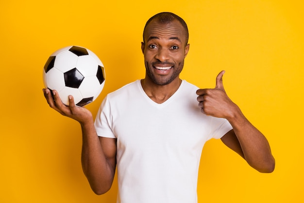Gai positif formateur coach guy tenir ballon de football lever le pouce vers le haut