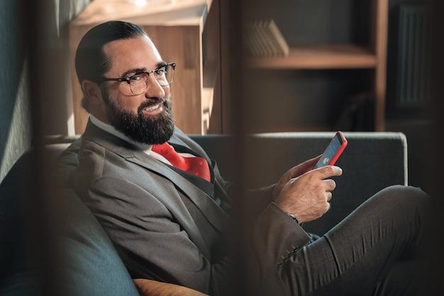 Gai et satisfait. homme d'affaires barbu se sentant joyeux et satisfait après négociation avec des partenaires
