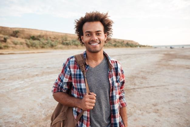 Gai séduisant jeune homme africain debout à l'extérieur et tenant un sac à dos