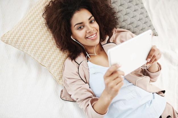 Gaie femme africaine en vêtements de nuit et casque souriant tenant la tablette allongée sur le lit.