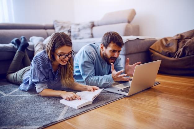 Gaie femme caucasienne allongé sur le sol et livre de lecture. son petit ami nerveux allongé à côté d'elle et regardant un ordinateur portable. intérieur du salon.