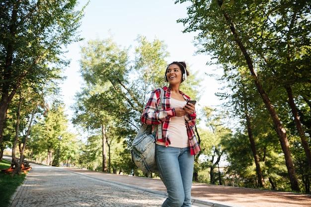 Gaie jeune femme africaine marchant à l'extérieur