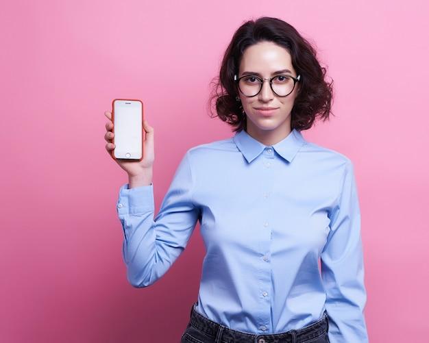 Gaie jeune femme à l'aide de smartphone avec un casque sur fond rose