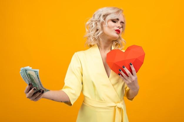 Gaie jeune femme aux cheveux blonds courts sourit et choisit entre l'amour et l'argent isolé sur orange