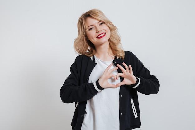 Gaie jeune femme dans des vêtements décontractés faisant un geste du cœur avec les mains