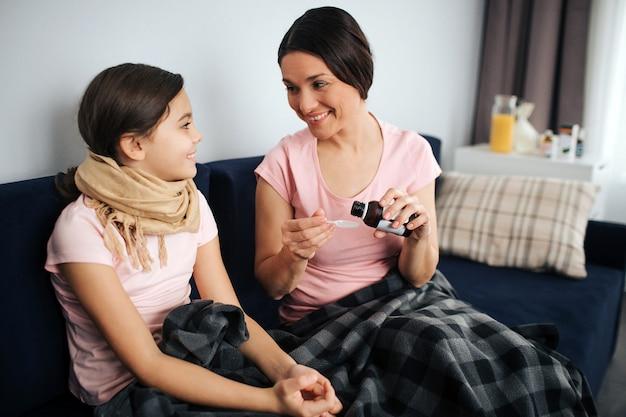Gaie jeune femme et fille s'asseoir ensemble sur le canapé et sourire
