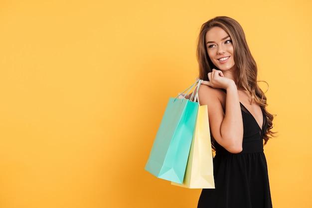 Gaie jeune femme en robe noire tenant des sacs à provisions.