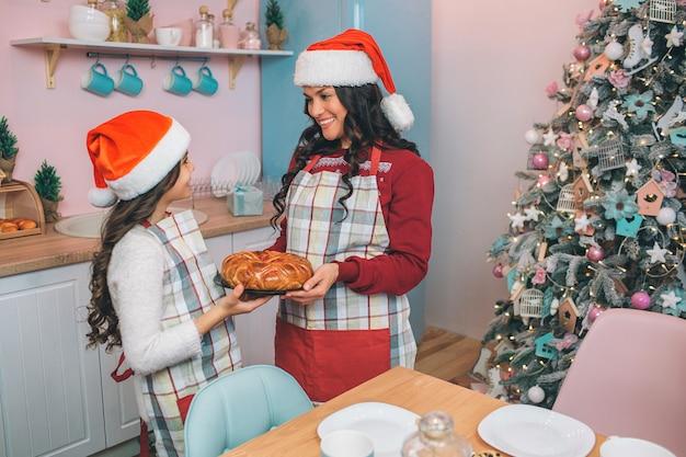 Gaie jeune femme se tient devant sa fille et la regarde. elle sourit. la femme porte un tablier et des vêtements de fête avec un chapeau rouge. fille regarde sa mère. ils tiennent la tarte ensemble.