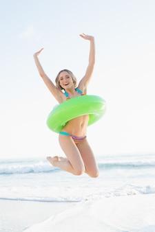 Gaie jeune femme tenant un anneau de caoutchouc tout en sautant sur une plage