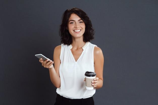 Gaie jeune femme tenant son téléphone et son café dans les mains