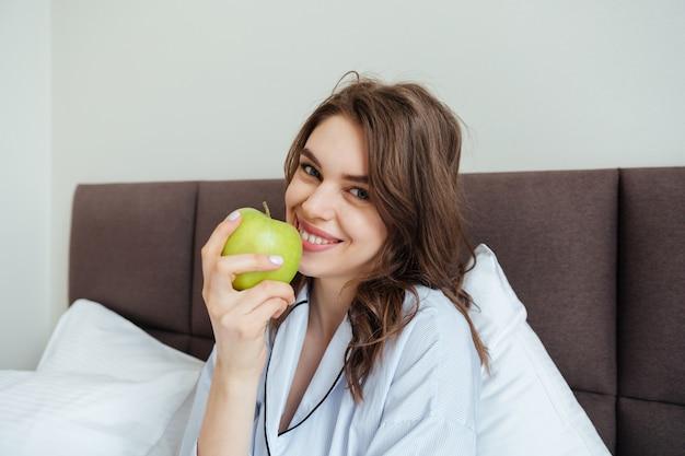 Gaie jeune femme vêtue de pyjama mange une pomme.