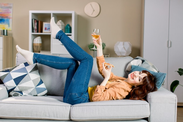 Gaie jeune fille en jeans et chemise jaune, tenant un verre de vin et un morceau de pizza, en position couchée sur un canapé gris dans une chambre confortable