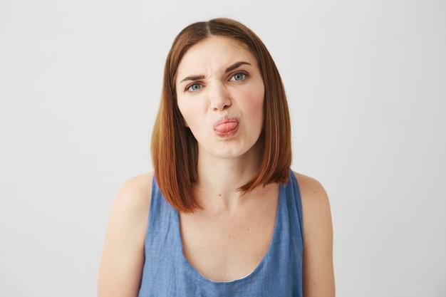 Gaie jeune jolie fille brune montrant la langue faisant la grimace.