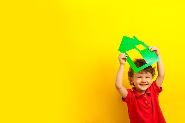 Gaiement enfant tient une maison verte au-dessus de sa tête. bonne enfance, restez à la maison positive avec la famille et les enfants.