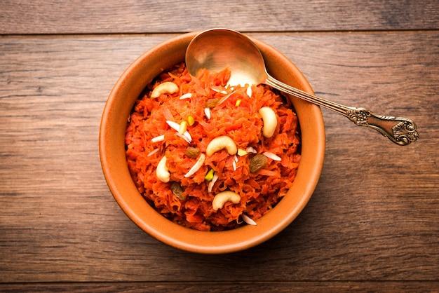 Gajar ka halwa est un pudding sucré à base de carottes originaire d'inde. garni de noix de cajou aux amandes. servi dans un bol.