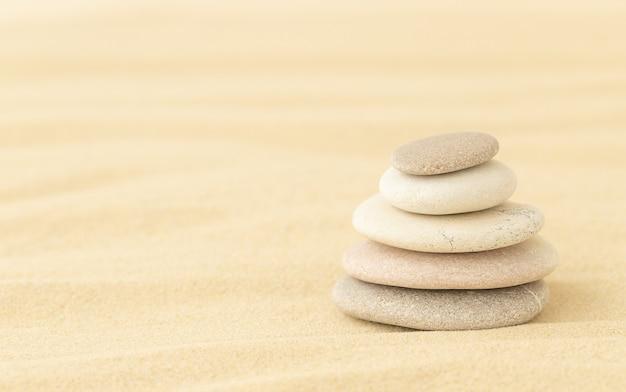 Galets de mer empilés les uns sur les autres sur le sable