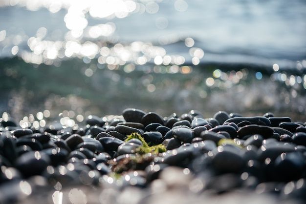 Galets de plage avec bokeh de soleil étincelant et vagues de mer mousseuses