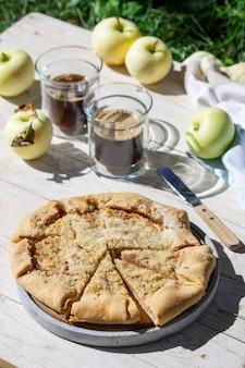 Galette aux pommes et streusel aux noisettes, servie avec du café sur un fond en bois. style rustique.
