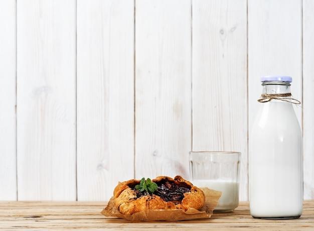 Galette aux prunes, un verre de lait et une bouteille de lait