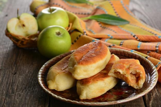 Galette chaude avec des pommes vertes fraîches sur fond de bois