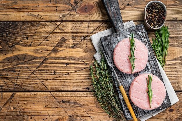 Galette de hamburgers crus à partir de viande de poulet et de dinde bio au thym et au romarin. fond en bois. vue de dessus. copiez l'espace.