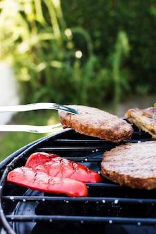 Galette prise avec une pince et des légumes grillés