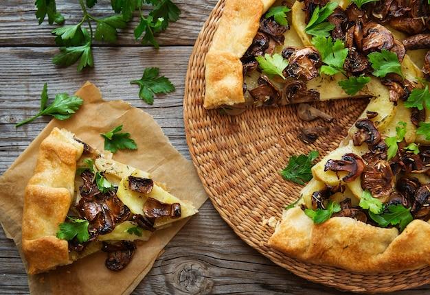 Galette salée avec pommes de terre, champignon et verdure sur un bois