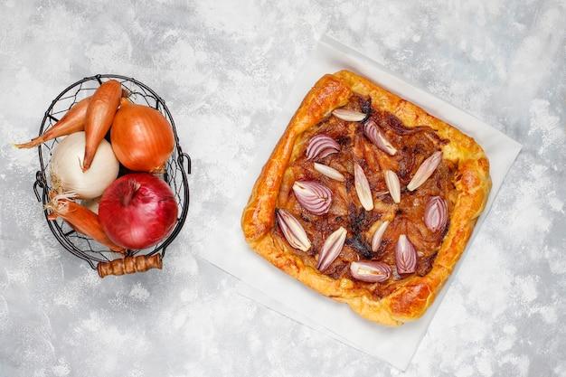 Galette de tarte à l'oignon à la française avec pâte feuilletée et divers oignons, échalotes, oignons rouges, blancs et jaunes, vue de dessus