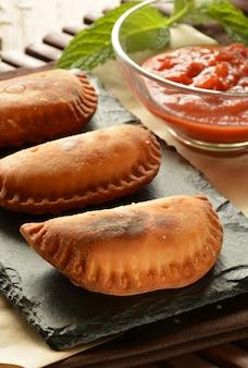 Galette de thon maison à la sauce tomate sur une table en bois