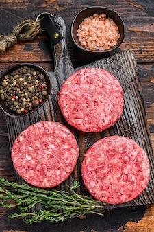 Galettes de burgers de steak cru avec du boeuf haché et du thym sur une planche à découper en bois