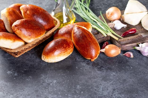 Galettes fraîches cuites au four farcies aux œufs et aux oignons verts. table marron foncé. pirozhki salé traditionnel russe et ukrainien. style rustique. copiez l'espace.