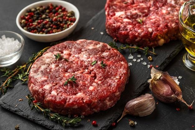 Galettes de hamburgers de bœuf à la viande hachée fraîche sur une ardoise noire avec des épices et des herbes pour la cuisson sur une surface noire. fermer