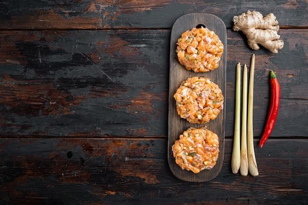 Galettes de poisson cru avec filet de saumon et citronnelle, sur la vieille table en bois, mise à plat avec un espace pour le texte