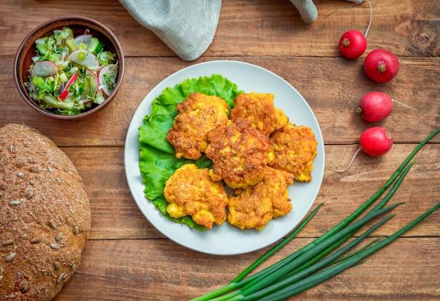 Galettes de poulet maison, servies sur une assiette, salade, pain, oignon vert et radis sur table en bois.
