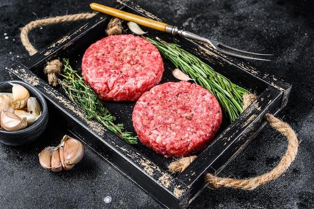Galettes de viande de bœuf crue pour hamburger à partir de viande hachée et d'herbes sur une planche de bois