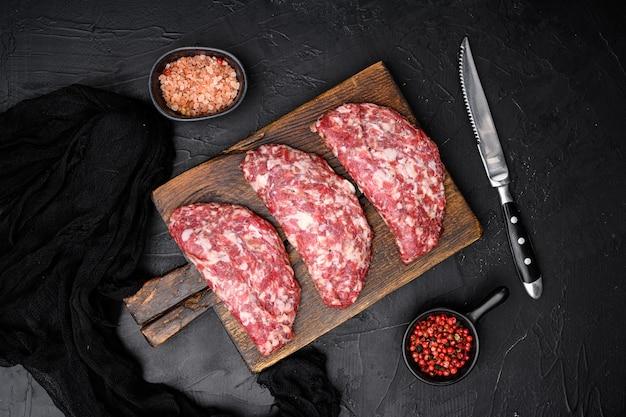 Galettes de viande crue hachée. ensemble de galettes de viande, sur fond de table en pierre noire noire, vue de dessus à plat