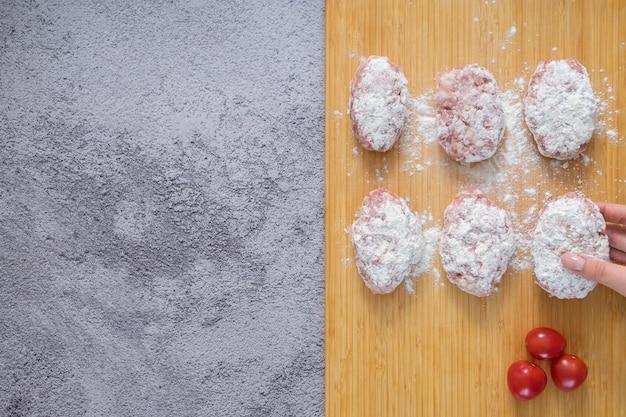 Galettes de viande crue pour la friture. le processus de cuisson des boulettes de viande.