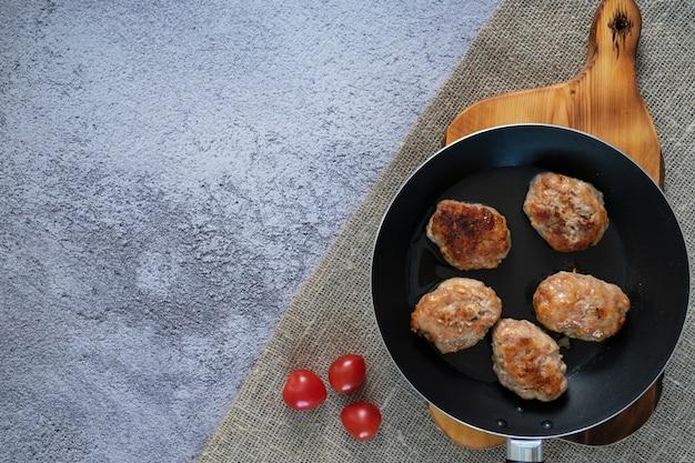 Des galettes de viande prêtes dans une poêle sur la table. main avec une fourchette.