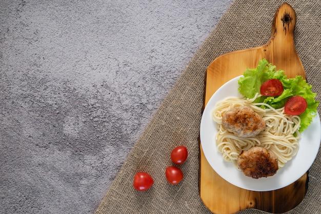 Des galettes de viande avec de la salade dans une assiette sur la table. plat fait maison.
