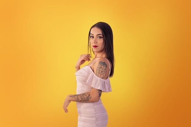 Gama,distrito federal, 16 octobre 2021, jeune femme en robe courte dans des poses sexy sur fond jaune.