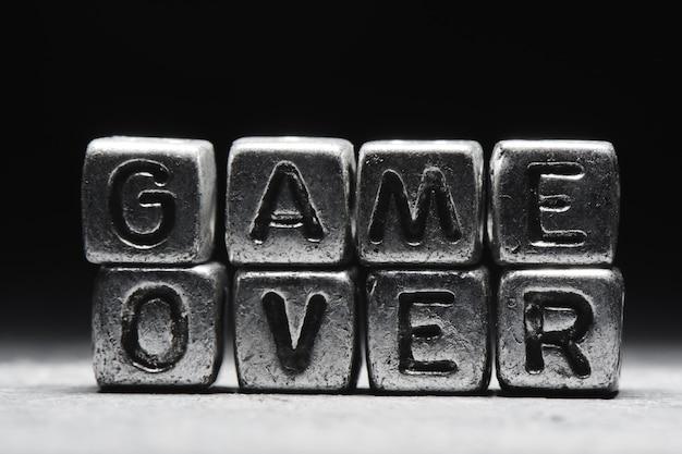Game over concept. inscription 3d sur des cubes métalliques dans un style grunge sur fond noir gris isolé