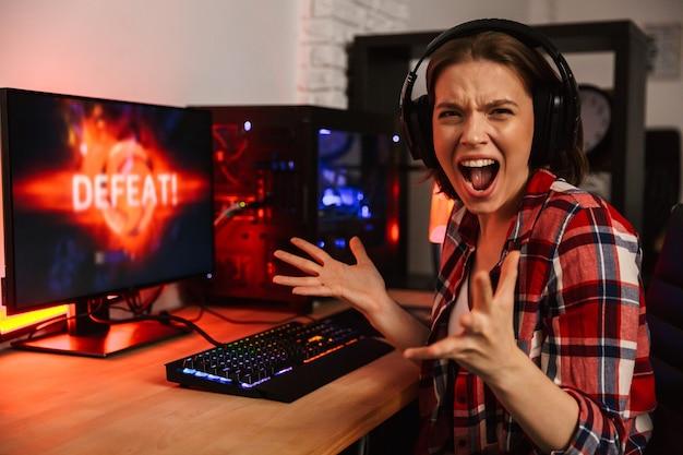 Gamer femme en colère assis à la table, jouer à des jeux en ligne sur un ordinateur à l'intérieur